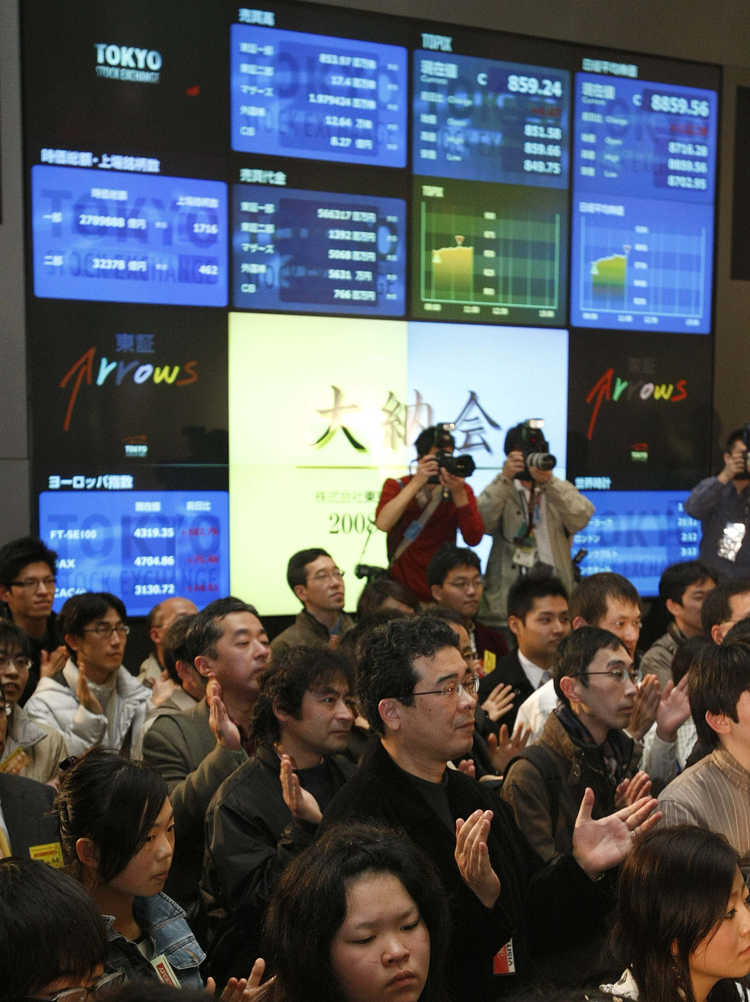 Securities brokerage officers, employees and visitors applaud during a ceremony marking the end of trading for 2008 in front of an electronic board di...