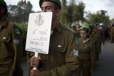 An Israeli soldier holds the sign name as others carry the coffin of 2nd Lt. Roy Peles, an infantry officer, during his funeral at Kiryat Shaul milita...