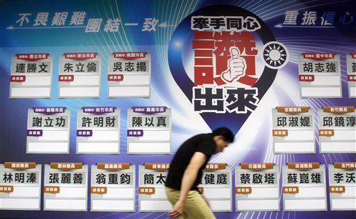A staff of Taiwan's ruling Nationalist Party walks past a poster of candidate list with empty data at the headquarter in Taipei, Taiwan, Saturday, Nov...