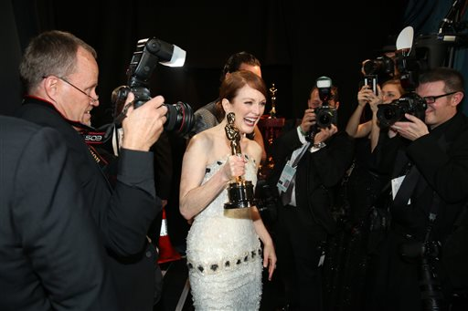 """Julianne Moore is photographed backstage with her award for best actress in a leading role for """"Still Alice"""" at the Oscars on Sunday, Feb. 22, 2015, a..."""