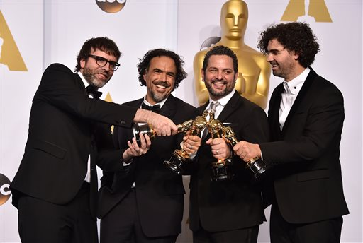 Nicolas Giacobone, and from left, Alejandro Gonzalez Inarritu, Alexander Dinelaris and Armando Bo pose in the press room with the award for the best p...