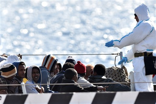 "An Italian Navy officer gives instruction to migrants who are waiting to disembark from Italian Navy ship ""Driade"" in Messina's port, Sicily, Italy, S..."