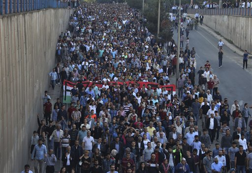 Protesters march to protest Saturday's explosions in Diyarbakir, Turkey, Sunday, Oct. 11, 2015. Turkey declared three days of mourning following Satur...