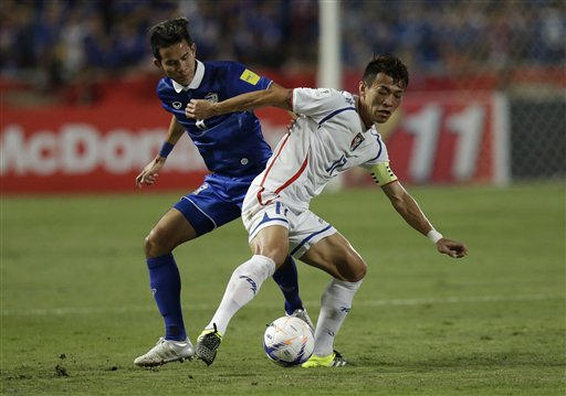 Sanrawat Dechmitr of Thailand , left, and Chen Po Liang of Taiwan battle for the ball during their World Cup qualifying soccer match at Rajamangala na...