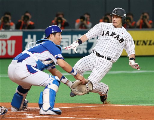 Japan's Nobuhiro Matsuda, right, crosses home plate after Japan's Hayato Sakamoto hit a sacrifice fly against South Korea during the second inning of ...