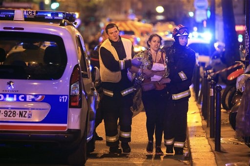 Rescue workers help a woman after a shooting, outside the Bataclan theater in Paris, Friday Nov. 13, 2015. French President Francois Hollande declared...