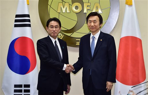 South Korean Foreign Minister Yun Byung-Se, right, and his Japanese counterpart Fumio Kishida pose for a photo at the start of their meeting at Foreig...