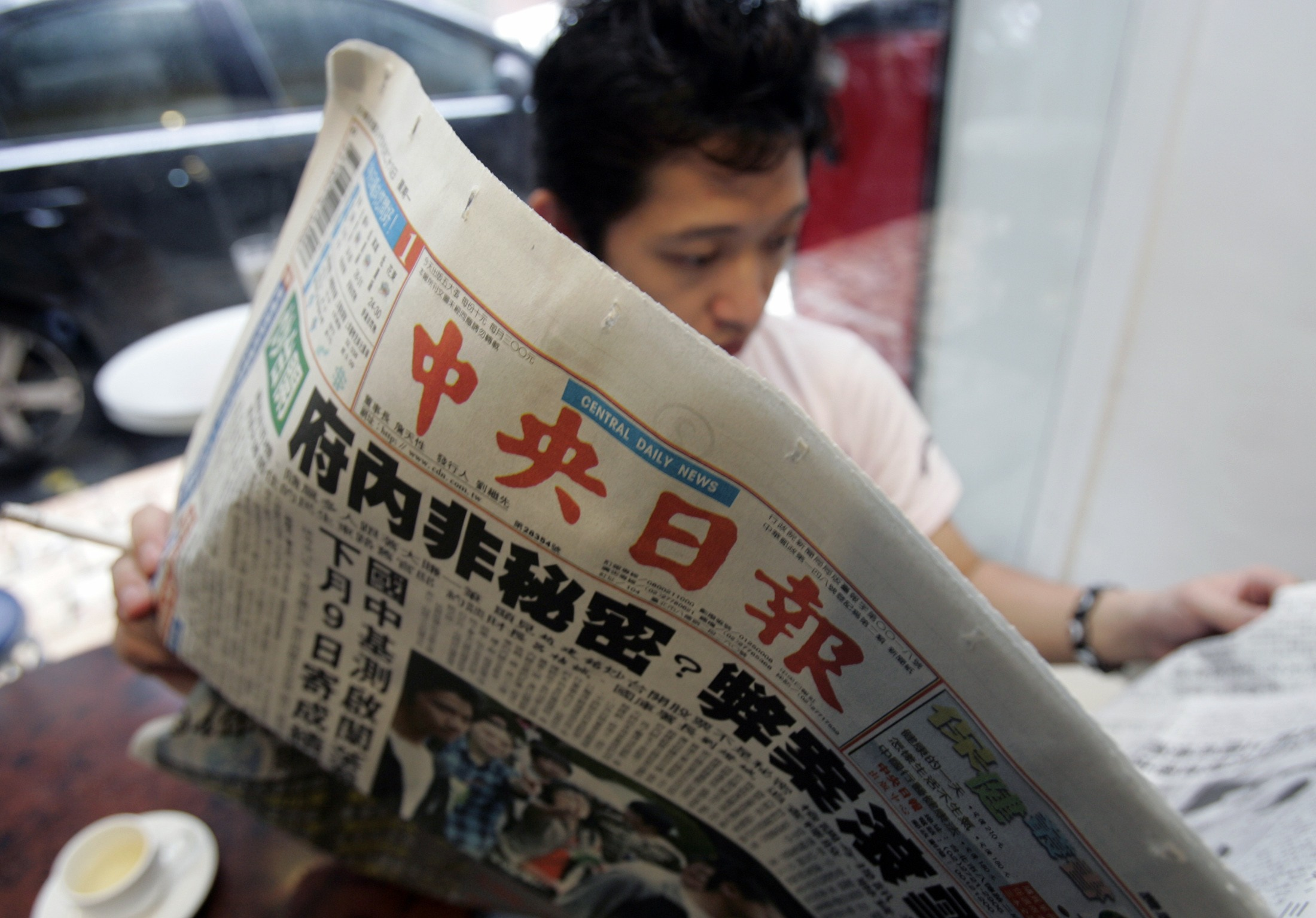 A man reads the Central Daily News in Taipei May 29, 2006. The 78-year-old newspaper, which is owned by the Nationalist Party or Kuomintang (KMT), is