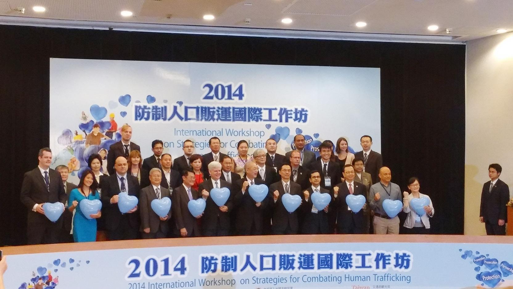 吳敦義副總統(前排中),移民署署長莫天虎(前排右5),各國駐我國辦事處代表及與會貴賓手拿藍色心型氣球合照。