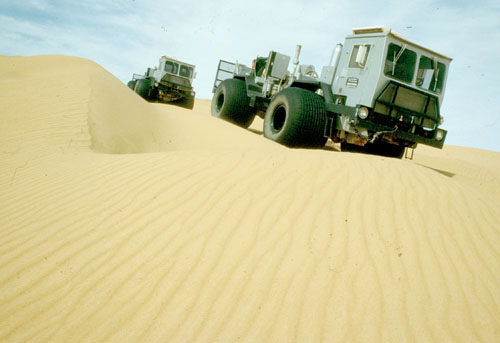 Trucks shoot seismic surveys detailing rock structures underneath Sahara sand dunes in Libya in this file photo. The surveys are the first step in oil...