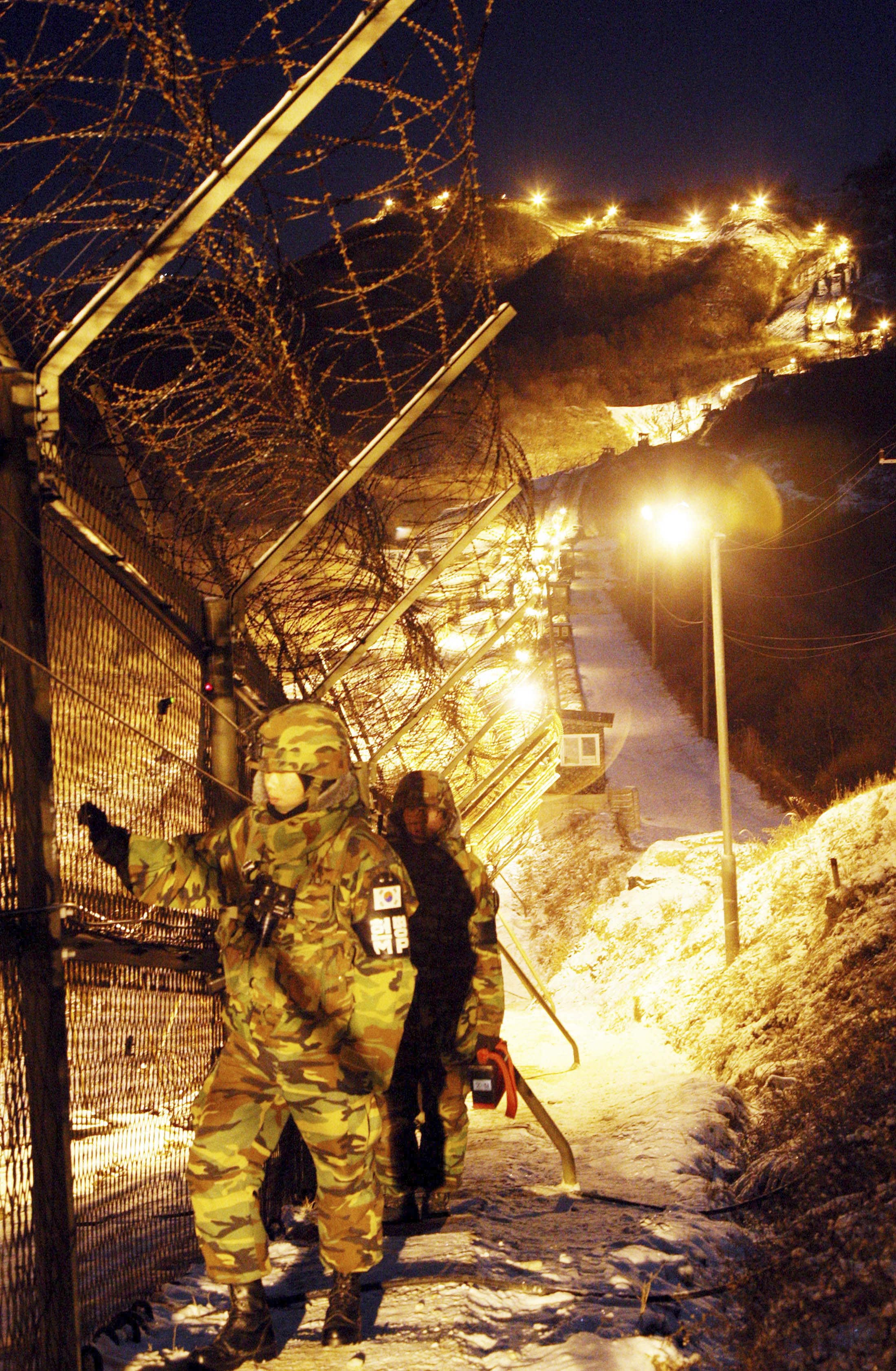 South Korean Army soldiers patrol along the barbed-wire fence in the early morning at the demilitarized zone(DMZ) in Hwacheon, north of Seoul, South K...