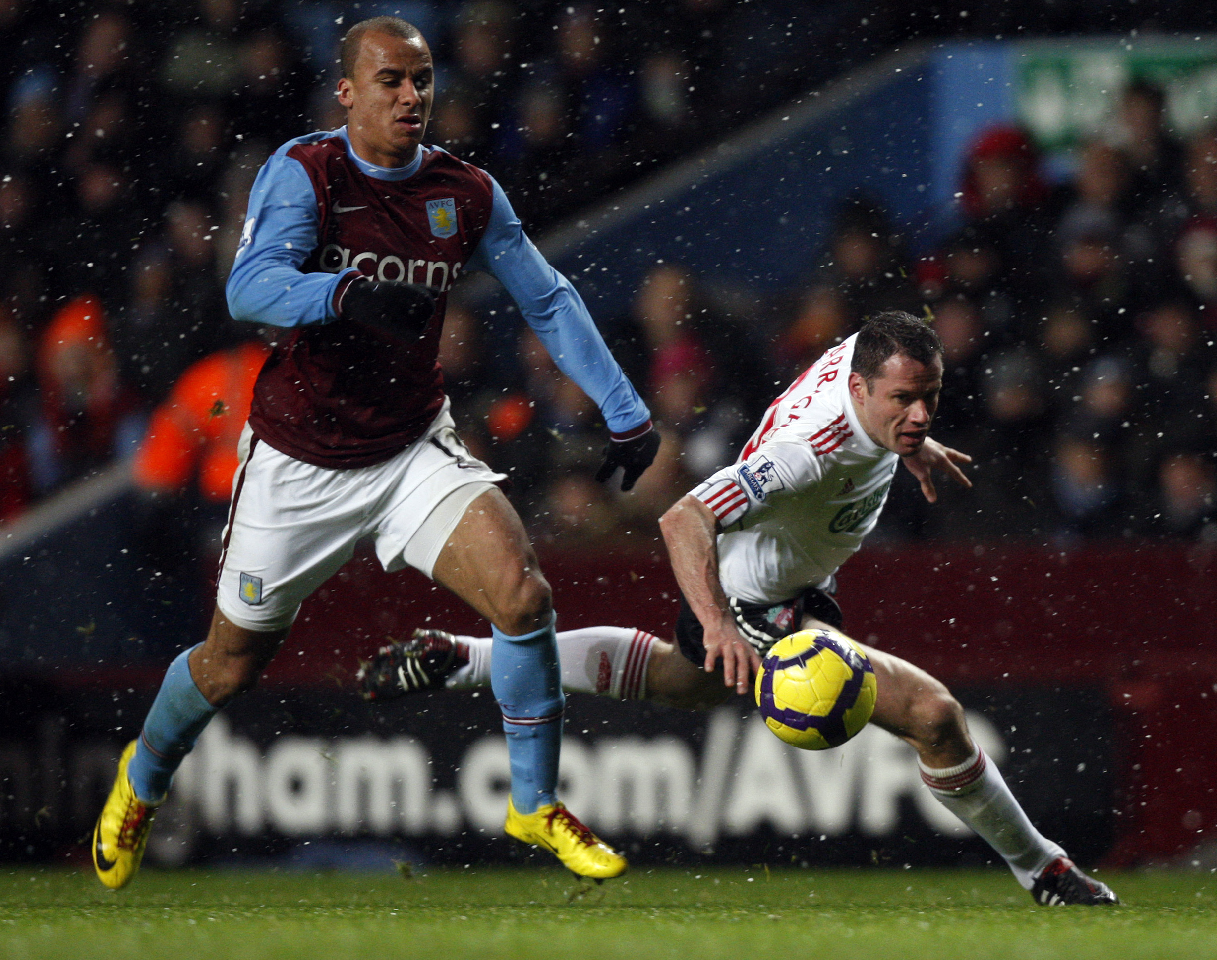 Aston Villa's Gabriel Agbonlahor, left, vies for the ball with Liverpool's Jamie Carragher as he falls during their English Premier League soccer matc...