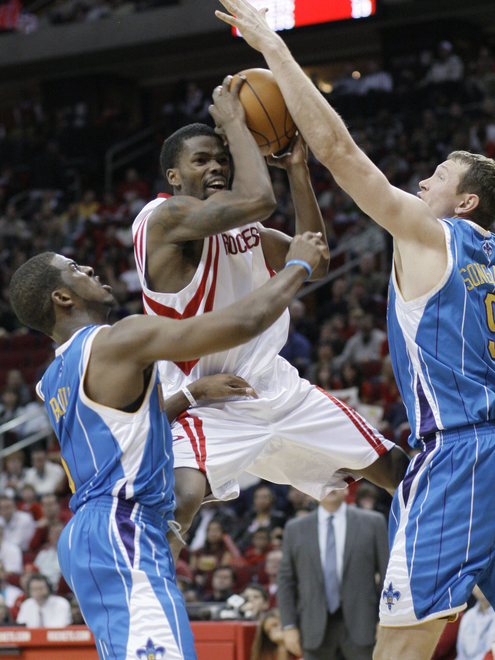Houston Rockets' Aaron Brooks, center, goes to the basket between New Orleans Hornets' Chris Paul, left, and Darius Songaila, of Lithuania, during t...