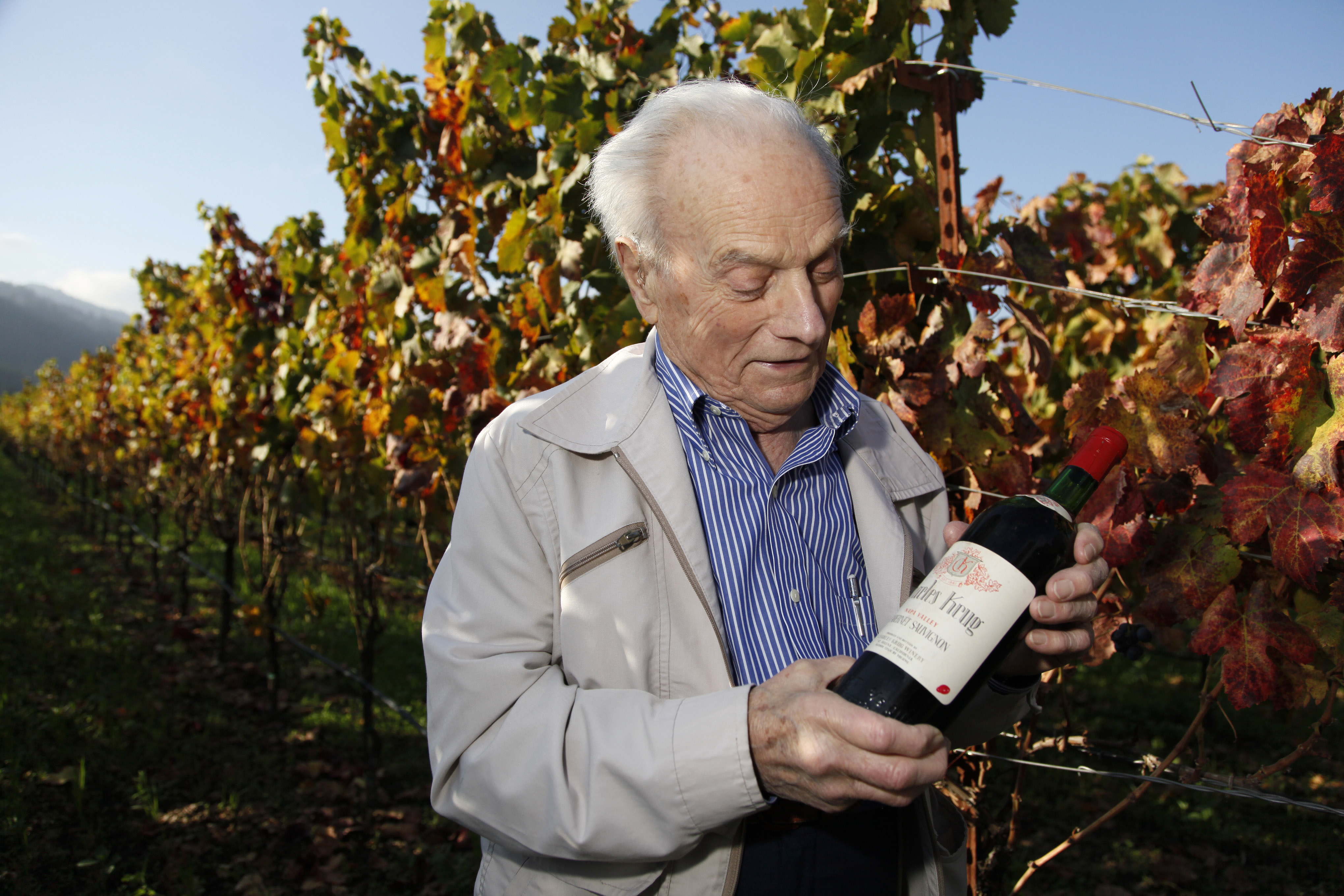 Peter Mondavi Sr. looks at a bottle of 1944 Charles Krug Cabernet Sauvignon, the first his family produced, while standing in a vineyard at the winery...
