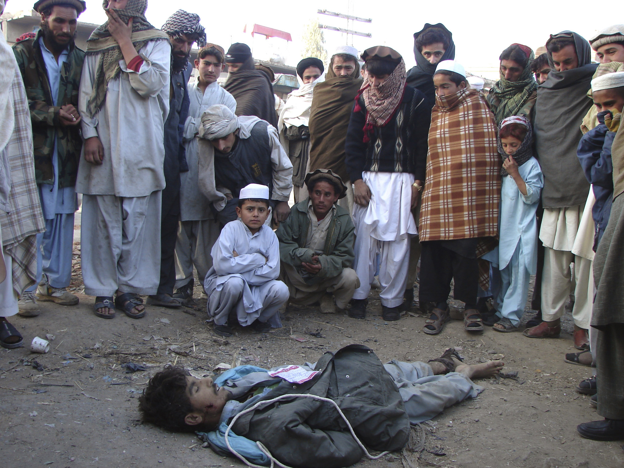 Pakistanis surround the body of an Afghan national who was allegedly killed by the al-Qaeda-linked Haqqani network for spying in Pakistan's tribal are...