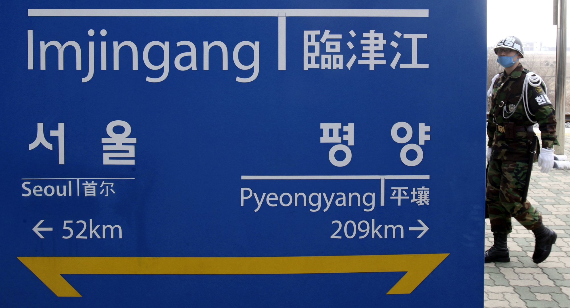 A South Korean military police walks by a directional sign showing distances to North Korea's capital Pyongyang and that for South's capital Seoul at ...