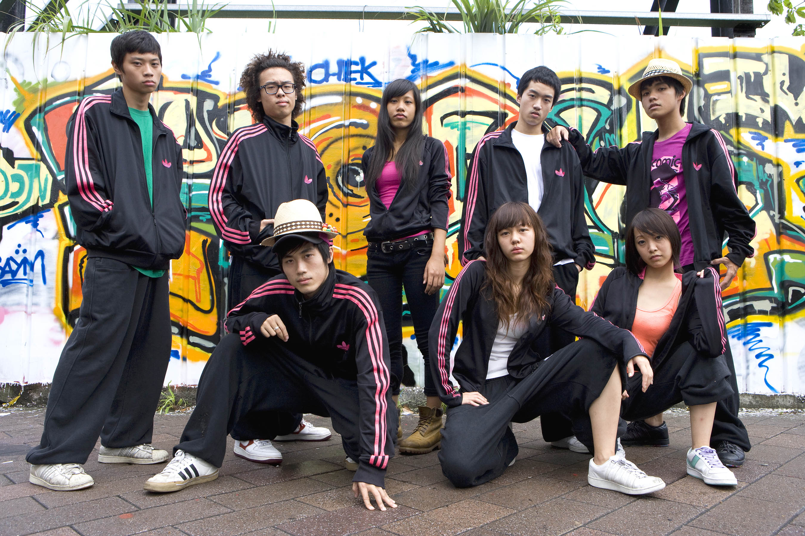 A 17-year-old troupe of street dance, Undergradu-Eight, pose in front of a graffiti wall. (Photo Courtesy of Flash Forward Entertainment)