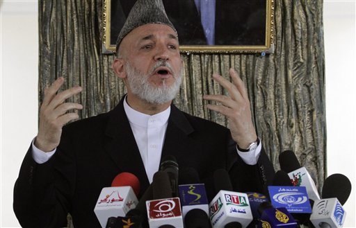 Afghan President Hamid Karzai talks to Afghans in Argandab district of Kandahar province, south of Kabul, Afghanistan on Saturday. Karzai flew to sout...