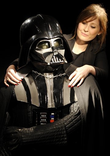 Christie's employee Caitlin Graham poses with a Darth Vader costume in London, England today. The helmet, mask, shoulder armour and shin guards of the...