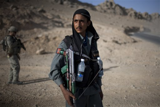 An Afghan policeman takes a break in a check point on the outskirts of Kandahar City, Afghanistan yesterday.