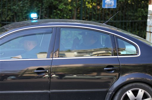 A police car carries two men, not seen inside car, who were detained after an explosion at a private delivery company in Athens, Greece on Monday. A w...