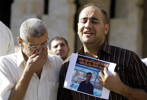 Udai Saadallah, right, holds a photo of his slain brother, Iraqi priest Thair Saadallah, during his funeral in Baghdad, Iraq yesterday. The priest was...