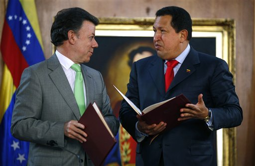Colombia's President Juan Manuel Santos, left, and Venezuela's President Hugo Chavez hold bilateral agreements at Miraflores presidential palace in Ca...