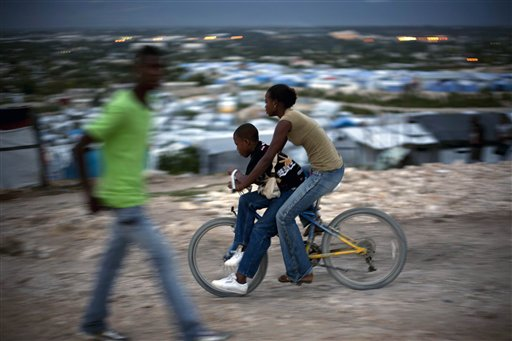 People ride a bicycle as they enter the Caradeux Camp for people displaced by the Jan. earthquake in Port-au-Prince, Haiti on Tuesday. Forecasters pre...