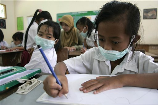 School children wear masks to protect their respirations from volcanic ash spewed by erupting Mount Merapi in Cangkringan, Yogyakarta, Indonesia yeste...