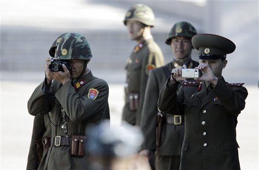 North Korean soldiers take pictures south side during a repatriation ceremony at the border village of the Panmunjom (DMZ) that separates the two Kore...