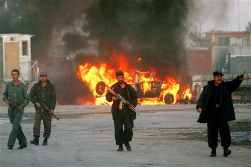 In this November 2005 file picture, police officers secure the area in front of a burning international peacekeeper vehicle after a second suicide att...