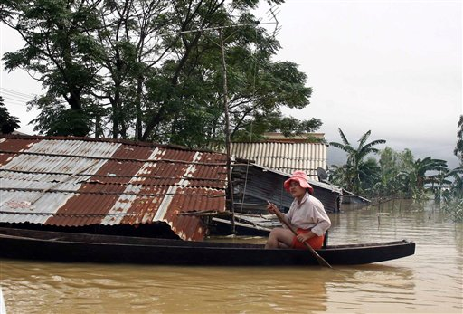 A woman guides her small boat past a flooded home in central Quang Binh province, Vietnam on Oct. 17. Heavy rains have killed at least 16 people and l...