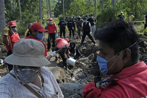 Civil protection and forensic workers recover a body which was buried at a field in the town of Tuncingo, southern Mexico yesterday. Authorities recov...
