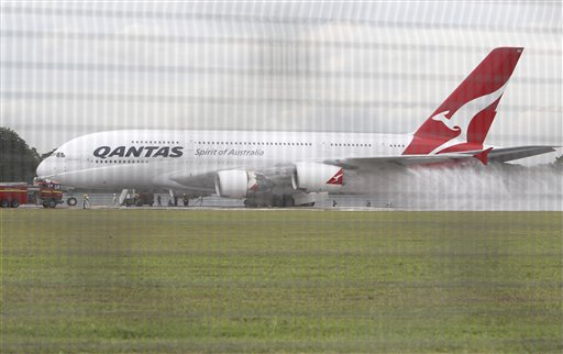 Firefighters surround a Qantas passenger plane which made an emergency landing in Singapore's Changi International Airport after having engine problem...