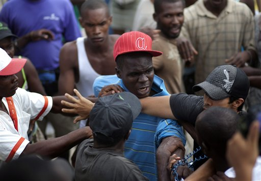 A foreign volunteer, right, intervenes in a scuffle between earthquake survivors who were listening the call to evacuate the Corail-Cesselesse refugee...