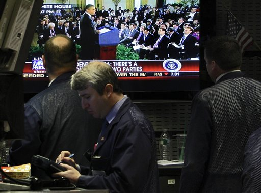 Traders watch President Barack Obama's White House news conference on a television screen on the trading floor of the New York Stock Exchange yesterda...