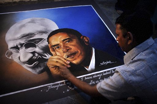 In this photo taken yesterday, an Indian artist works on a painting of President Barack Obama and the late Indian leader Mahatma Gandhi at his studio ...