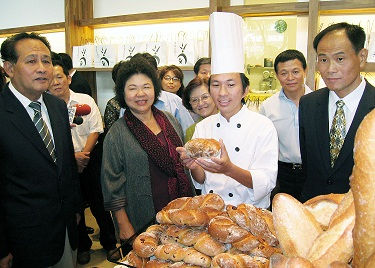 Kaohsiung Mayor Chen Chu, center left, and award-winning baker Wu Pao-chun, center right, pose in front of a lot of delicious bread at the newly opene...