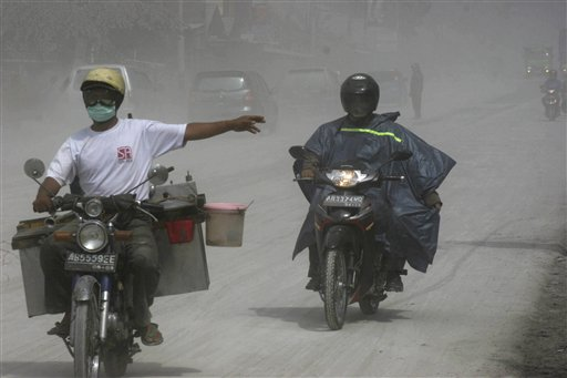Motorists ride on a street covered with volcanic ash from the eruption of Mount Merapi in Muntilan, Indonesia today. Indonesia's deadly volcano sent a...