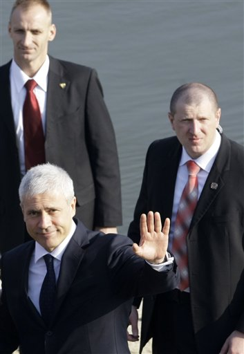 Serbian President Boris Tadic, left, escorted by bodyguards waves in Vukovar, Croatia today. Tadic is to pay his respects to 200 Croats slain by Serbs...