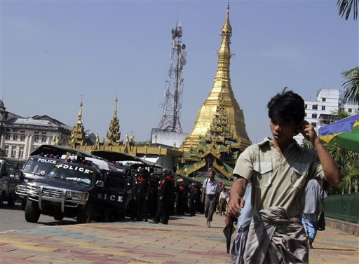 Pedestrians walk past riot police trucks stationed outside the City Hall today in downtown Yangon, Myanmar. The military government has tightened secu...