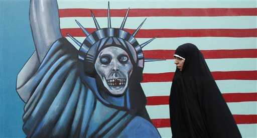 A head-to-toe veiled Iranian woman walks past a satirized drawing of the Statue of Liberty, painted on the wall of the former U.S. Embassy in Tehran, ...