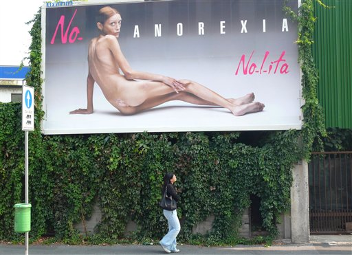 In this Sept. 25, 2007 file photo, a woman looks at a giant poster showing French model Isabelle Caro, part of a campaign against anorexia by Italian ...
