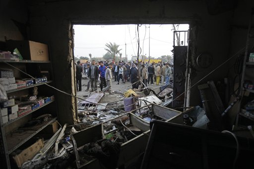 People gather around a destroyed shop at the scene of a car bomb attack in Baghdad, Iraq yesterday. A car bomb ripped through a funeral tent in a main...