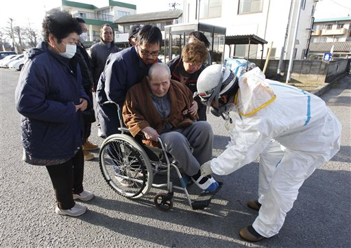 An elderly man is helped into a wheelchair to be scanned for levels of radiation in Koriyama, Fukushima Prefecture, Japan yesterday.