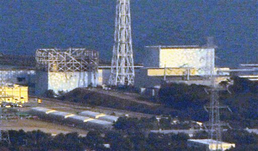 In this photo taken on Sunday, the damaged Unit 1, left, and Unit 2, right, of the Fukushima Dai-ichi nuclear plant are seen in Okumamachi, Fukushima ...