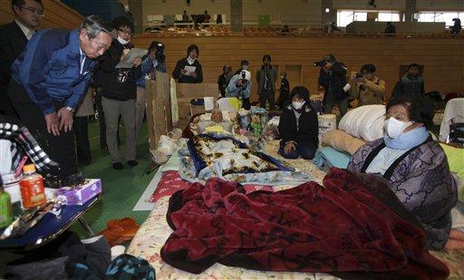 Norio Tsuzumi, vice president of Tokyo Electric Power Co. (Tepco), left, apologizes evacuees at an evacuation center in Tamura of Fukushima Prefecture...