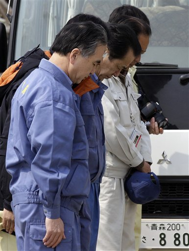 Japan's Prime Minister Naoto Kan, center, bows for the victims of the March 11 earthquake and tsunami-destroyed town of Rikuzentakata, Iwate Prefectur...
