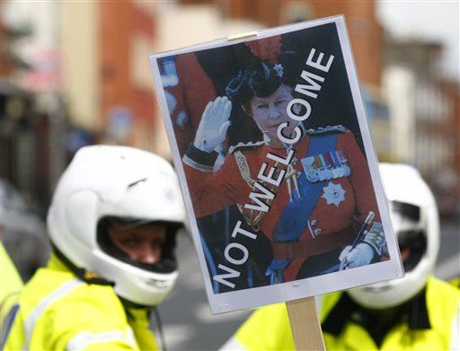 An anti-British protestor holds up a placard bearing the image of Britain's Queen Elizabeth II in front of police lines in Dublin yesterday. The Queen...