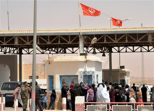 Libyans flee from fighting as they cross the Dhiba border between Libya and Tunisia yesterday.